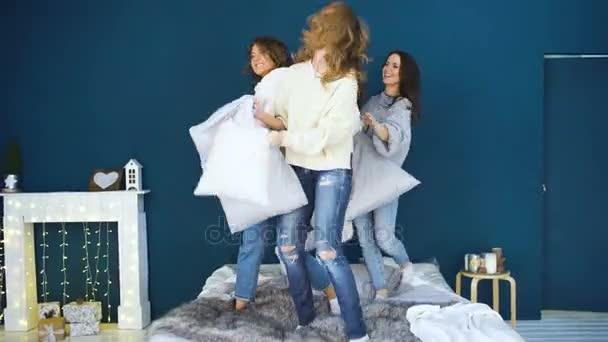 Négy gyönyörű lány harcot párnák egymást. Barátnők szórakozás és nevetés a hálószobában