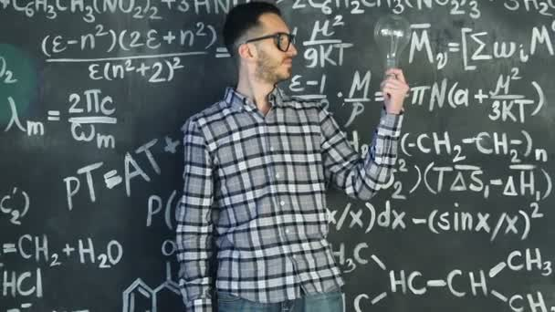 Young scientist man stand with lamp in chemical and mathematical equations wall room interior