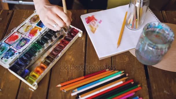 Mladá žena umělec kreslit pictrure akvarel barvy a štětce, míchání barev closeup