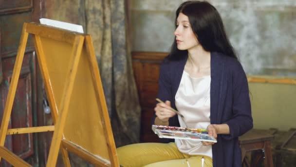 Giovane donna artista disegnare pictrure con vernici dellacquerello e spazzola su tela cavalletto