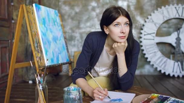 Giovane donna artista disegnare pictrure con pitture ad acquerello e sorriso loking in finestra