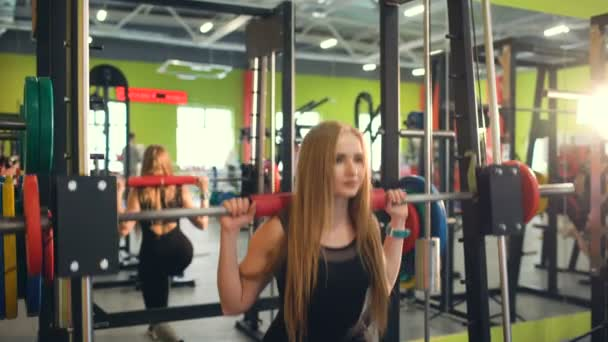 Silná blond žena dělá cvičení wtiht tréninků v fitnest klubu