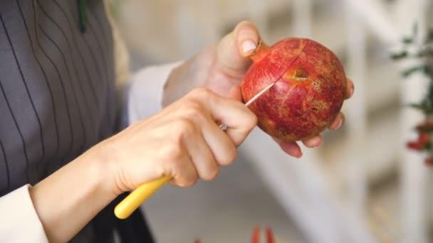 szakács nő szakács kötény vágott gránátalma kés closeup a konyhában