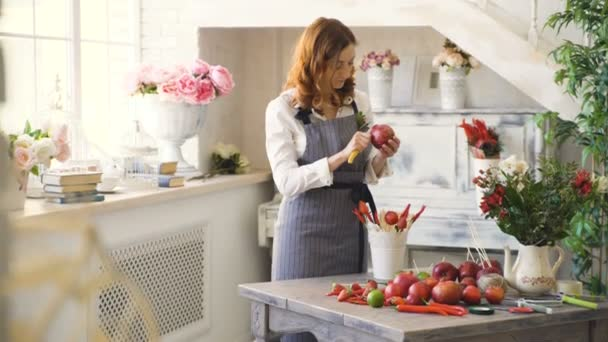 chef woman cook in apron cut pomegranate with knife neart fruits table in the kitchen