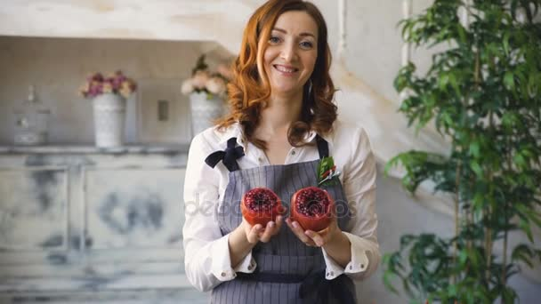 chef woman cook in apron shows pomegranate smiling into camera in the kitchen