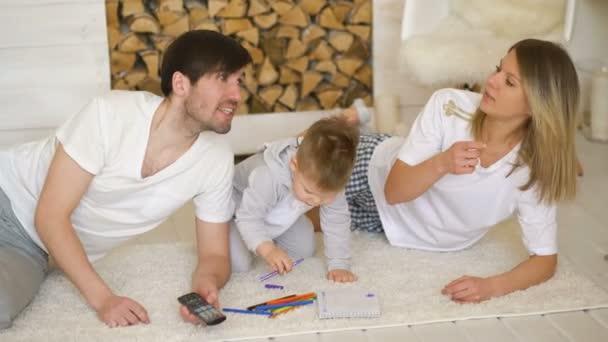 Otec matku stráž televizi, zatímco jejich syn nakreslit obrázek v jejich obývacím pokoji