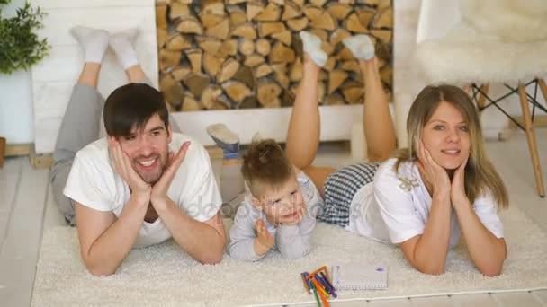 Portrait einer schönen Familie posieren und lächelnd am Boden in ihrem Wohnzimmer