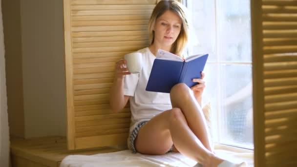 Krásná dívka v košili sedí u okna a čtení knihy a pití čaje