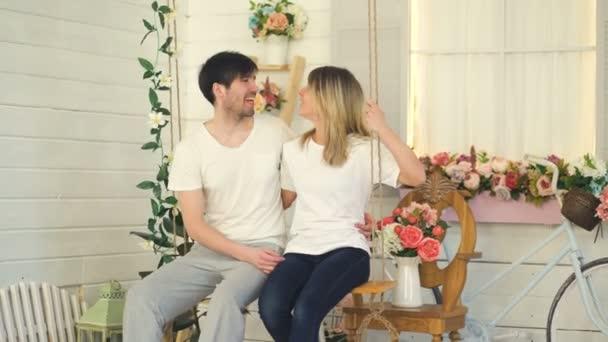 Šťastný, milující pár sedí v proudu a povídali, zatímco jejich syn hraje dveří v zahradě u domu