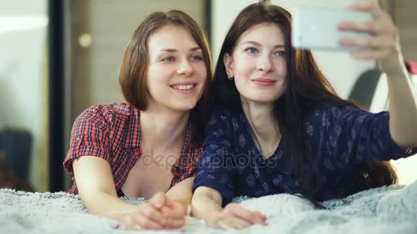 Két boldog nő meg, az ágyban fekve, és így selfie, reggel és érezd jól magad, ágy