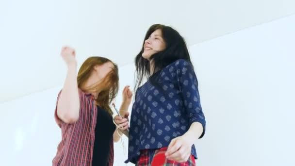Lassított lejátszás a fiatal boldog nők meg egy ágy-val fülhallgató tánc és érezd jól magad