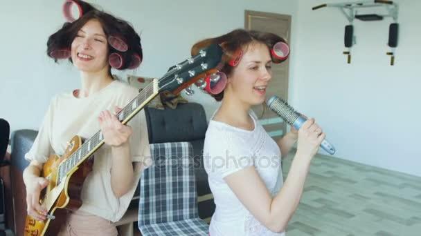 Zpomalený pohyb dvou vtipné dívky zpívat s hřebenem a hrát elektrická kytara tančit a zpívat