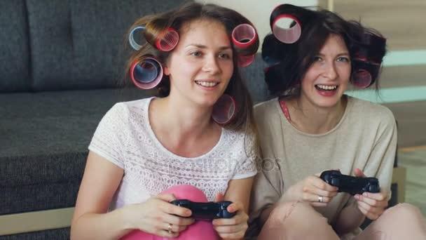 İki komik kadın ağır çekim konsol oyunları gamepad ile oynamak ve evde eğlenmek