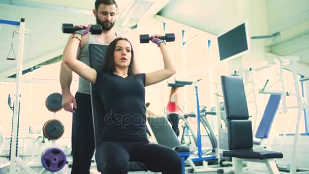 Trenér pomáhá mladá silná bruneta žena dělat cvičení v klubu a posilovnu fitcentrum