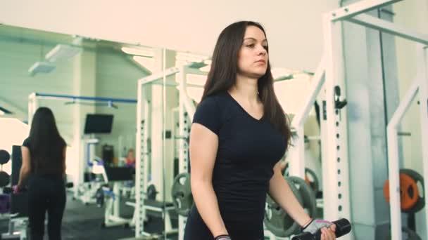 Silný brunetka žena dělá cvičení ve fitness klubu