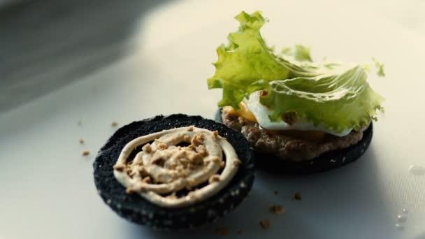 Closeup kuchaře vařit Grilovaná černé burgerwith omáčkou a zeleninou na kuchyňské desce