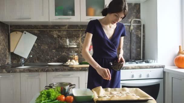 junge Köchin kocht in der heimischen Küche Gewürze in Platte mit Chicken Wings