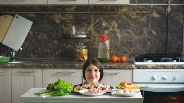 Portrét krásné usmívající se žena kuchař pořadu nad tabulkou se zeleninou v kuchyni doma