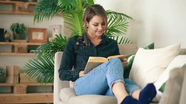 Šťastný dospívající dívka odpočívající na pohovce v obývacím pokoji při čtení její oblíbený román kniha doma
