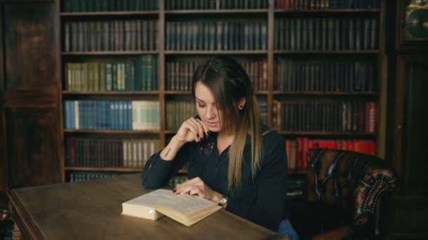 Fiatal, komoly nő olvasókönyv az egyetemi könyvtár beltéri