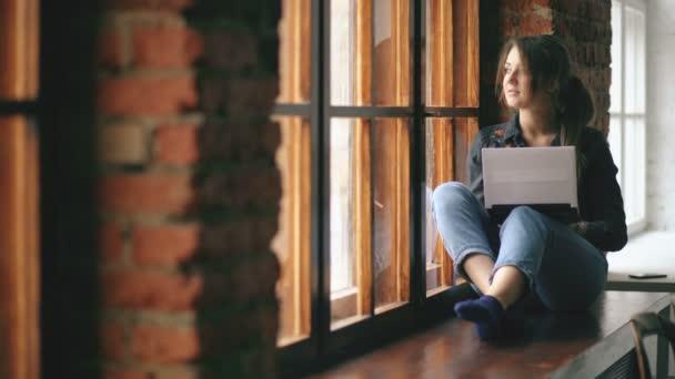 krásný mladý student dívka s notebookem sedět na parapetu v university učebna uvnitř