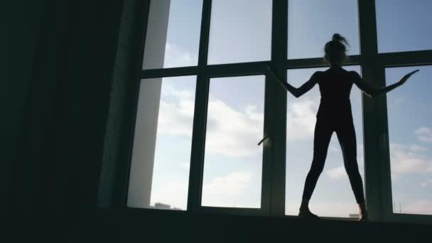 Sziluettjét fiatal lány táncos teljesítési kortárs tánc a tánc stúdió beltéri windowsiil