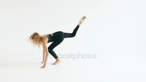 Zpomalený pohyb krásné dospívající dívka tanečnice tančí moderní na bílém pozadí uvnitř