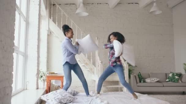 Vegyes faj fiatal csinos lányok ágyon ugrálás és szórakozás otthon párna küzdelem