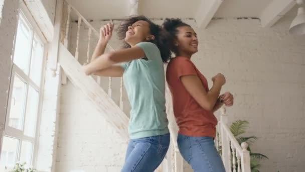 Vegyes verseny tánc egy ágyban együtt szórakozik fiatal gyönyörű nővérek hálószobában otthon szabadidős