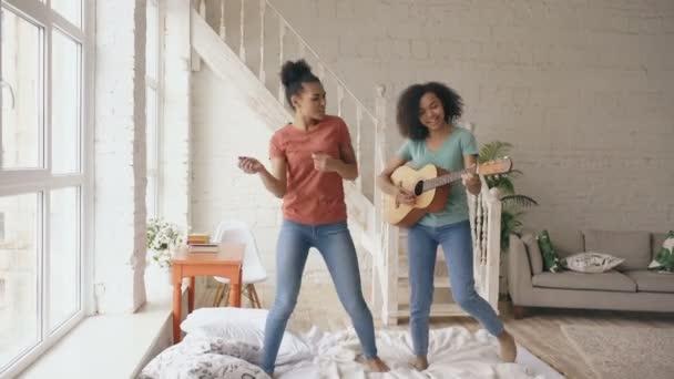 Vegyes faj fiatal vicces lány táncol, énekel és játszik akusztikus gitár, egy ágyban. Szórakozás nővérek hálószobában otthon szabadidős