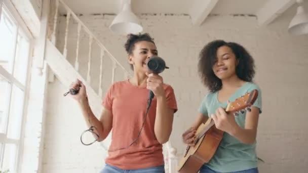 Vegyes faj fiatal vicces lányok tánc, éneklés, hajszárítóval és akusztikus gitáron játszik egy ágyban. Szórakozás nővérek hálószobában otthon szabadidős
