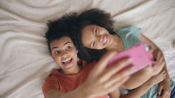 Felülnézet vidám kevert vicces nővérek, hogy selfie portré otthon hálószoba ágy