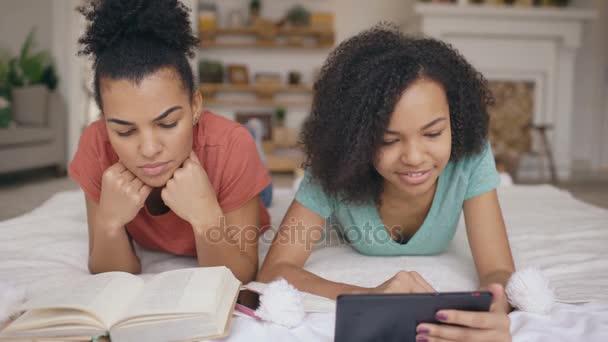 Két vidám vegyes verseny vicces barátnők könyvet olvas, és segítségével tabletta számítógép beszél és jó szórakozást, ágyban otthon