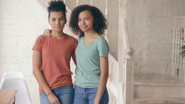 Portrét dvou krásných afrických amerických dívek směje a při pohledu do kamery. Ženy ukazují emoce z obličeje serios smát doma