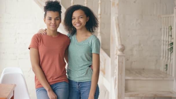Ritratto di due belle ragazze afroamericano ridendo ed esamina la macchina fotografica. Le donne mostrano emozioni da serios faccia ridere a casa