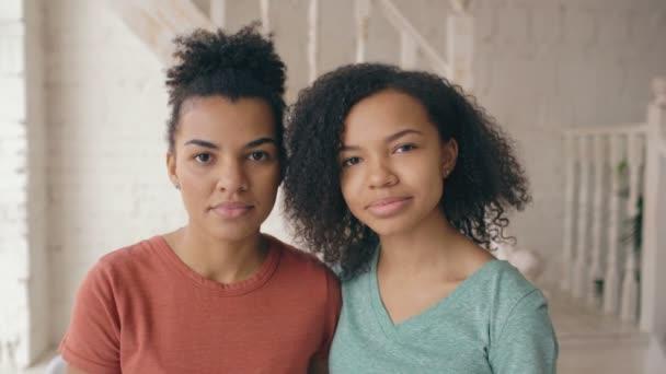 Closeup ritratto di due belle ragazze afroamericano ridendo ed esamina la macchina fotografica. Le donne mostrano emozioni da serios faccia ridere a casa