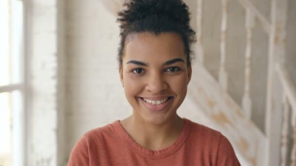 Detailní portrét krásnou americkou afričanku, směje se a při pohledu do kamery. Žena Ukázat emoce z obličeje serios smát doma