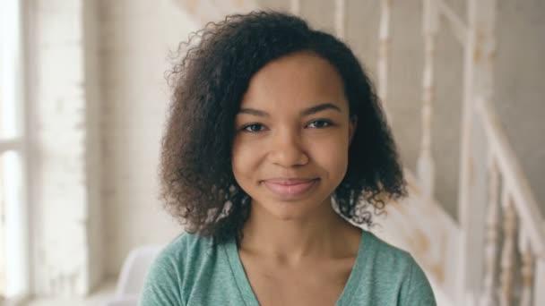 Vértes portréja szép afro-amerikai lány nevetett, és vizsgálja a kamera. Tinédzser mutatják, érzelmek a sorozat arc nevetni otthon