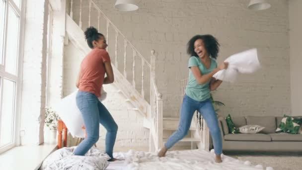 Zpomalený pohyb dvou mladých Smíšené rasy hezké dívky skákání na posteli a bojovat polštáře baví doma