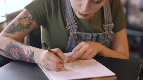 Mladá atraktivní žena s červenými vlasy tattoo umělec sedí u stolu a vytváření skici pro tetování ve studiu doma