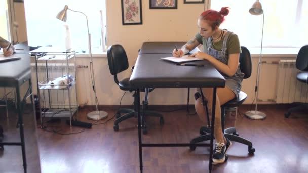 Vonzó fiatal vörös hajú nő tetováló művész asztalnál ül, és vázlatot tetoválás stúdió beltéri létrehozása