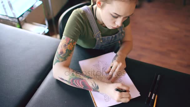 Pohled shora mladou atraktivní rusovláskou tatér sedí u stolu a vytváření skici pro tetování ve studiu doma