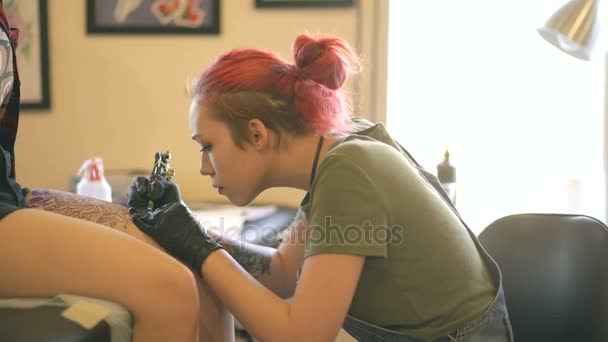 Young female red haired tattoo artist tattooing picture on leg of client over sketch in studio indoors