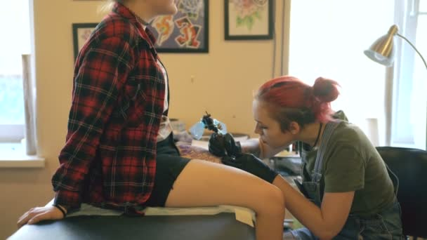 Red haired girl tattoo artist tattooing picture on lef of young girl client in studio