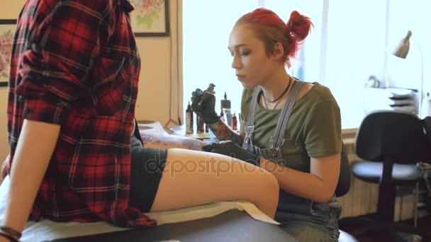 Fiatal női piros hajú tetováló művész tetoválás kép a lábát az ügyfél át vázlat bent a stúdióban