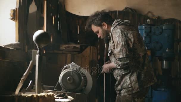 bärtiger junger Mann Schmied poliert in traditioneller Schmiede mit der Schleifmaschine von Hand Metallmesser
