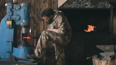 Slowmotion of bearded young man blacksmith using hydraulic press for steel arms manufacture at smithy workshop