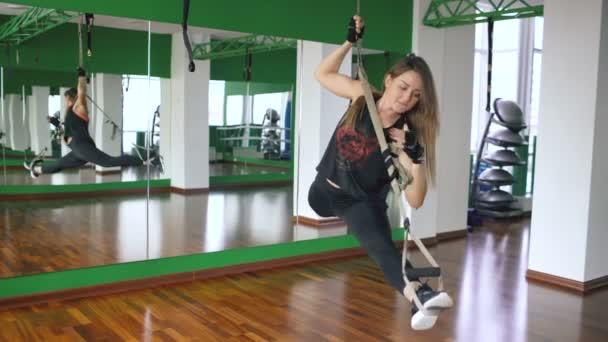 Mladá atraktivní žena v tělocvičně pracovali na trx a školení zbraní s fitness popruhy v tělocvičně