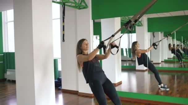 Mladá žena v tělocvičně pracovali na trx a školení zbraní s fitness popruhy v tělocvičně