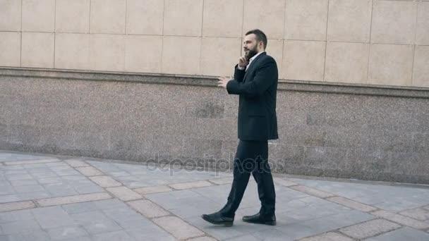 Dolly záběr mladých vousatý obchodní muž mluví na smartphone a cítí šťastní o tom, jak jednat procházky poblíž kancelářské budovy